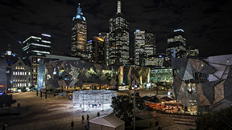 Circular light installation in front of Melbourne skyline